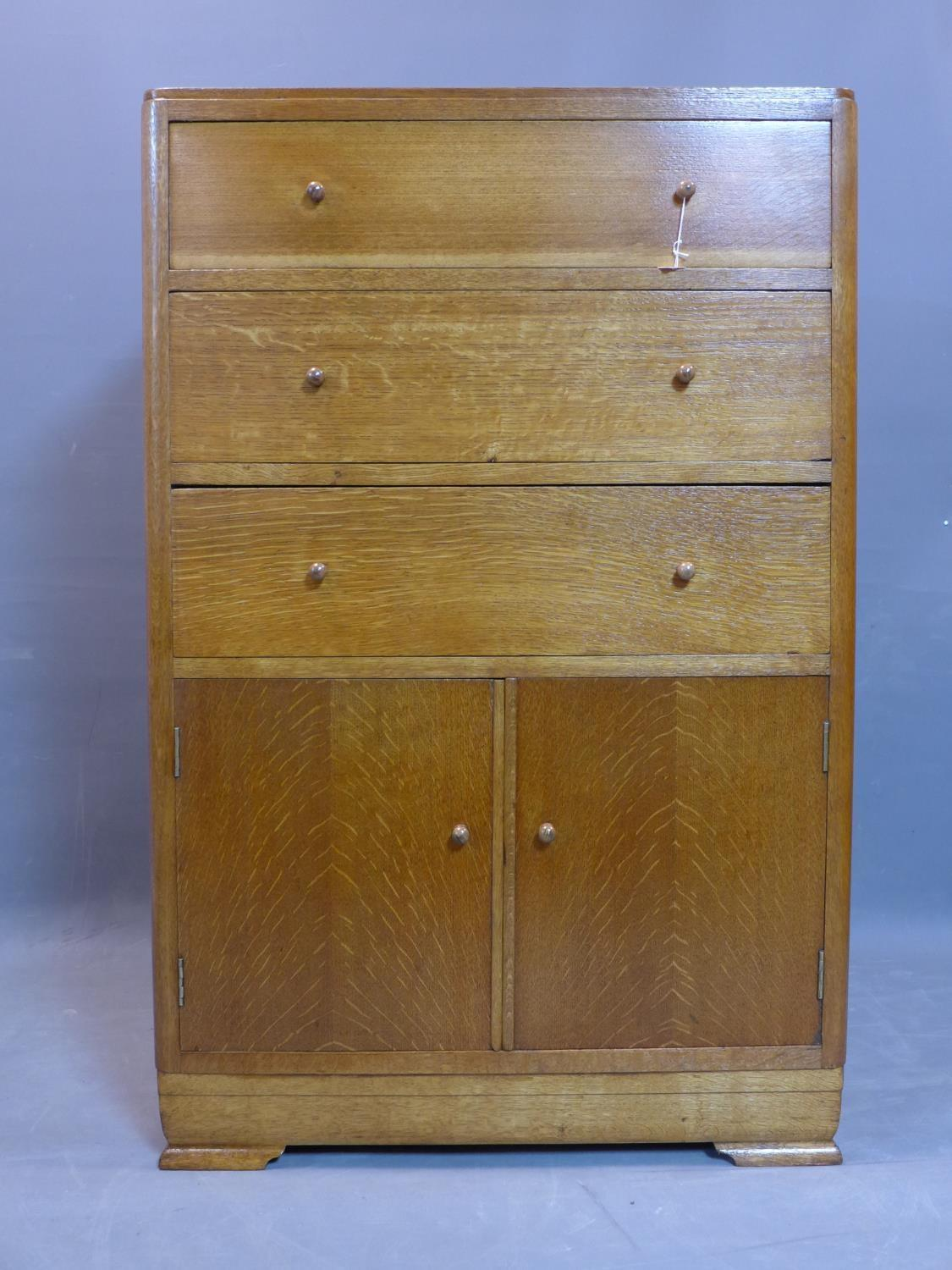 Lot 124 - An oak cabinet with three drawers above two cupboard doors, on bracket feet, H.115 W.75 D.48cm