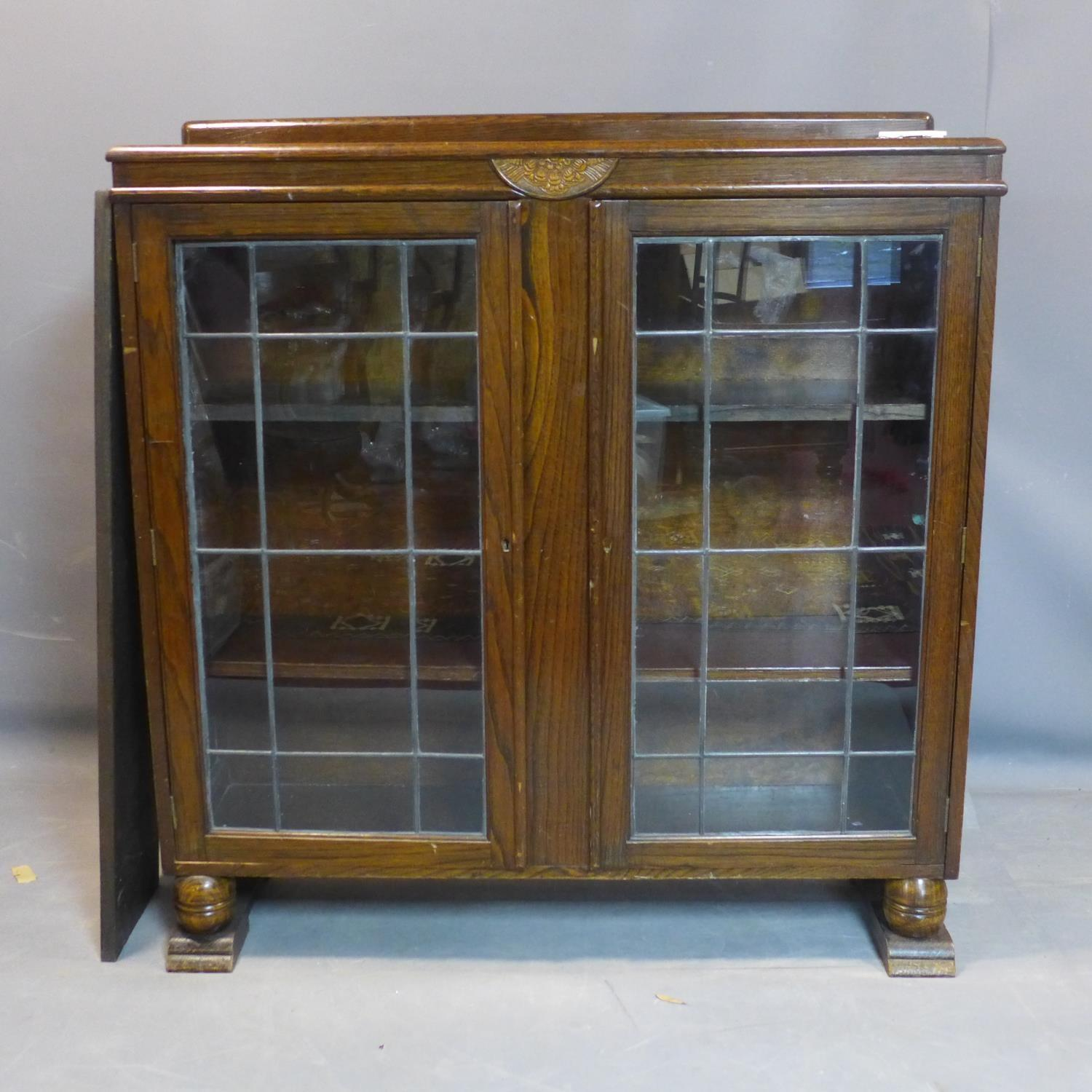 Lot 250 - An early 20th century oak glazed bookcase, with two leaded glass doors enclosing adjustable shelves,