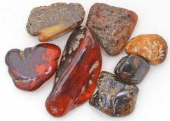7 Rohbernsteine.Unregelmäßig polierte Bernsteinstücke in verschiedenen Honigfarben, überwiegend