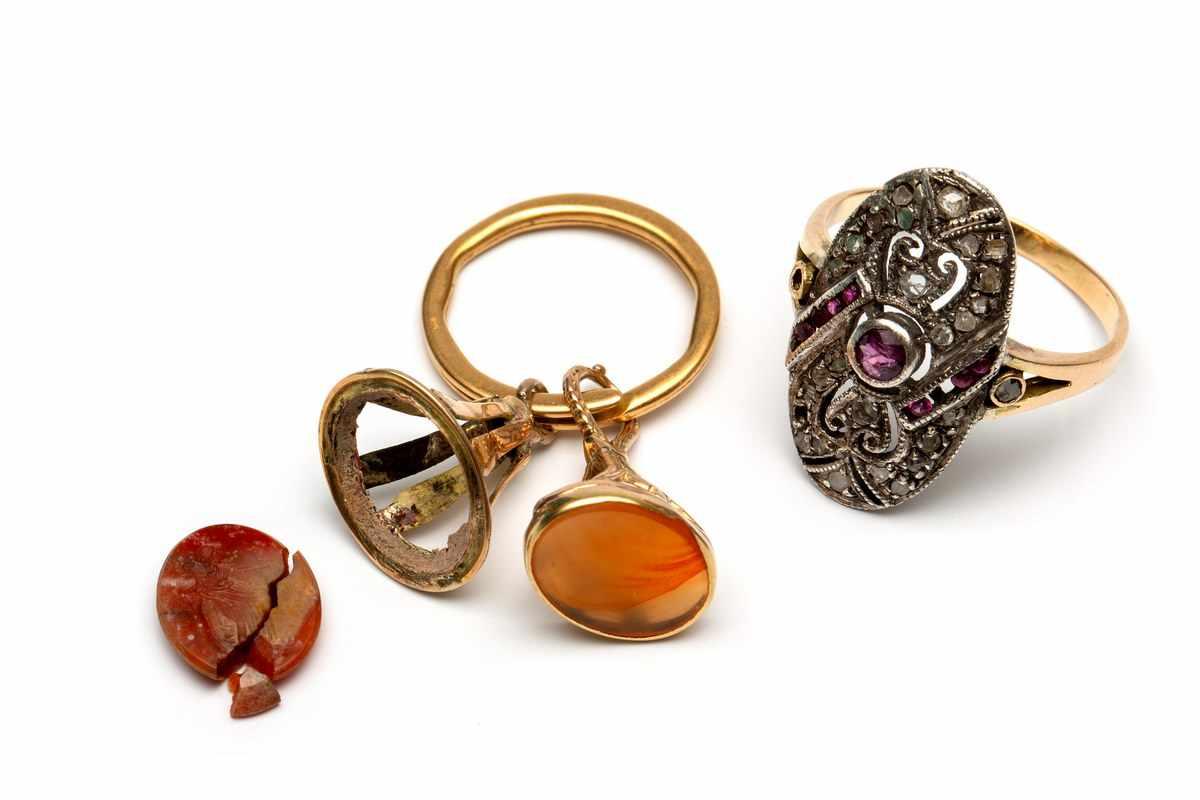 Lot 26 - Zilveren en gouden appliquering , twee gouden cachets aan 18krt. roségouden oog en een zilveren
