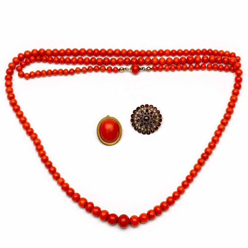 Lot 25 - Aflopend bloedkoralen collier en een 18krt. gouden broche tevens hanger,gezet met een ovale cabochon