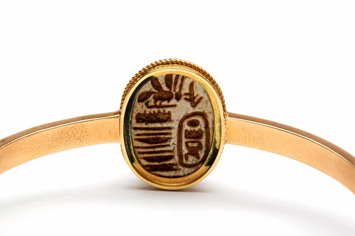 Lot 33 - Gouden stijve armbandin het midden een steatite scarabee, 15e dynastie (1479-1425 v Chr).