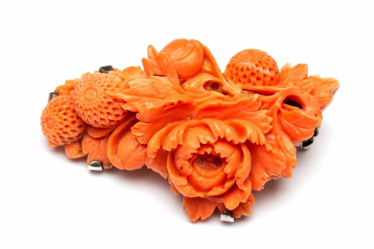 Lot 24 - Gesneden bloedkoralen broche, 19e eeuw,bestaande uit verschillende bloemen en knoppen. (
