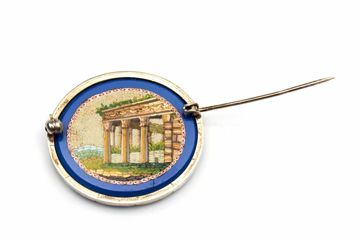 Lot 7 - Micro mozaïk broche, eind 19e eeuw,in zilveren montuur. Plaquette van blauwe agaat, aan één zijde