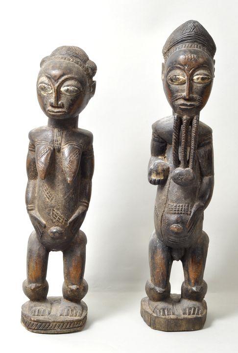 Lot 49 - Figurenpaar, Elfenbeinküste, BauleHolz, geschnitzt, schwarze krustige Patina, im Bereich der Augen