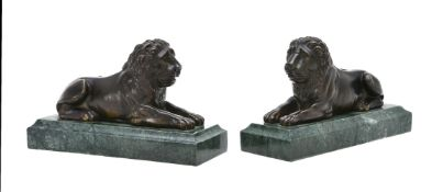 A pair of patinated bronze and marble mounted models of recumbent lions