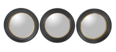 A set of three ebonised framed convex wall mirrors