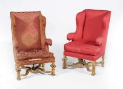 A companion pair of carved giltwood and upholstered wing armchairs