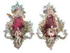 A pair of Meissen flower-encrusted allegorical two-branch wall appliques