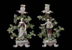 A pair of Bow figural candlesticks of a gardener and companion, circa 1765, modelled on scroll bases