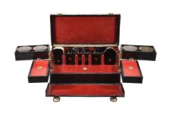 S. T. Dupont, a black leather travelling vanity case, 1930s, with a loop handle and brass clasps,
