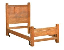 An Arts & Crafts oak Cotswold School single bed, circa 1910, probably by Heals or Liberty, the