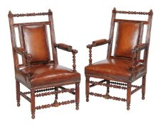A pair of Reformed Gothic walnut and leather upholstered armchairs, circa 1870, in the manner of