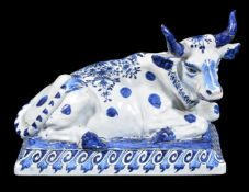 A Dutch Delft blue and white model of a recumbent cow, circa 1900, the underside with 'De Griekshe