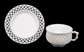 A Sevres white porcelain reticulated cup and saucer, 1873, cut with a quatrefoil band and border,