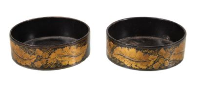 A pair of George IV painted and lacquered papier mâché bottle coasters