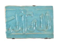 A small Kashan moulded turquoise glazed calligraphic tile Persia circa 13th century