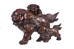 A Japanese Hinoki () Wood Sculpture of a mother shishi striding along with her two cubs