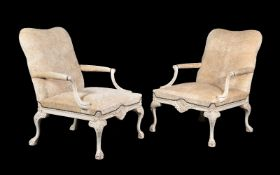 A pair of white painted and cut velvet upholstered elbow chairs, in George II style