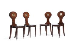 A set of four George III mahogany hall chairs