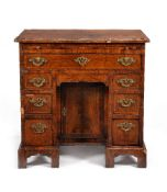 A George II figured walnut and feather banded kneehole desk