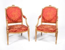 A pair of George III carved giltwood armchairs