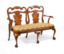 A figured walnut chair back settee, in George I style