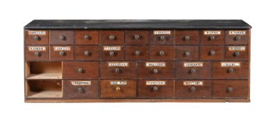 A mahogany apothecary cabinet with black marble top