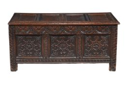 A carved and panelled oak coffer
