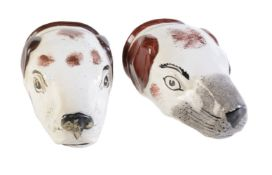 Two Staffordshire pottery hounds head stirrup cups painted with brown patches