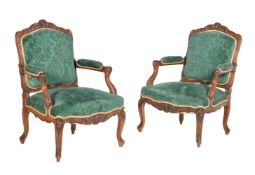 A pair of carved walnut armchairs in Louis XVI style