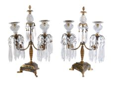 A pair of patinated and parcel gilt bronze and cut glass mounted twin light lustre candelabra in Reg