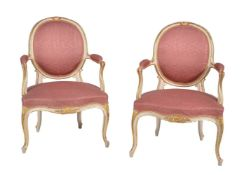 A pair of cream painted and parcel gilt armchairs