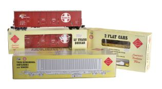 A collection of six Aristocraft railway box cars and low-loaders