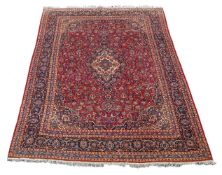 A Mashad carpet, North-East Persian, the vermillion central field decorated throughout with floral