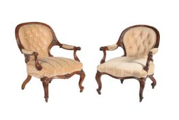A matched pair of Victorian walnut and upholstered open armchairs
