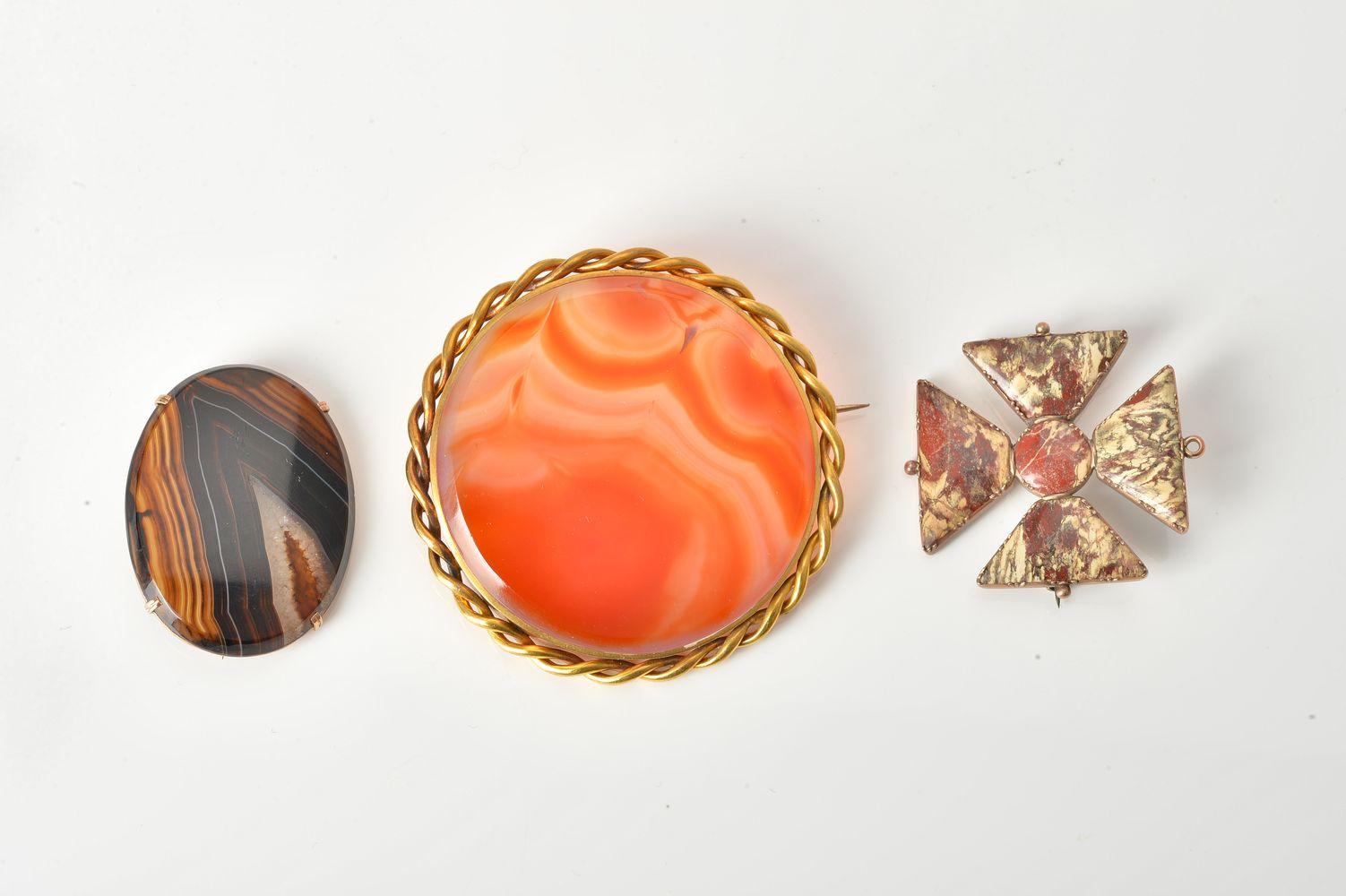 Lot 852 - Three hardstone brooches:- a mottled hardstone Maltese Cross brooch