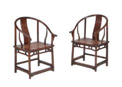 A pair of Chinese hardwood horseshoe-back armchairs