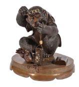 A Japanese Bronze Group of a Seated Monkey examining an Inro and its accompanying Manju Netsuke