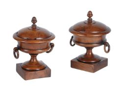 A pair of late George III turned yew wood urns and covers