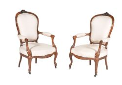 A pair of French carved fruitwood and upholstered fauteuils