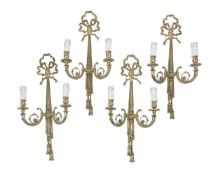 A set of four gilt metal twin light wall appliques in Louis XVI taste