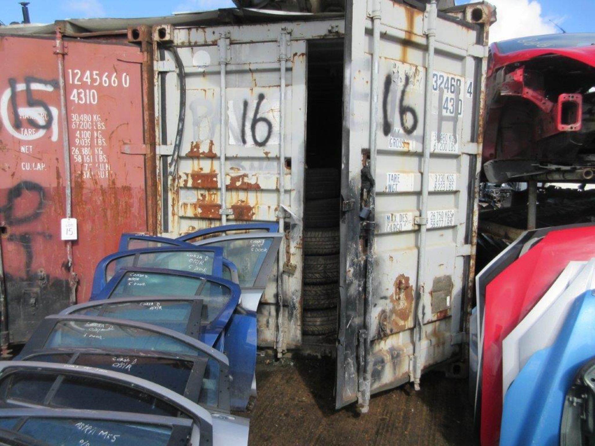 Lot 16 - Grey/white steel shipping container, 40 ft. x 8 ft. approx. plus racks and contents including tyres,