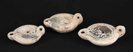 Drei ÖllampenRömisch, ca. 2.-3. Jh. n. Chr.. Terrakotta. Zwei Öllampen mit Reliefdarstellung eines