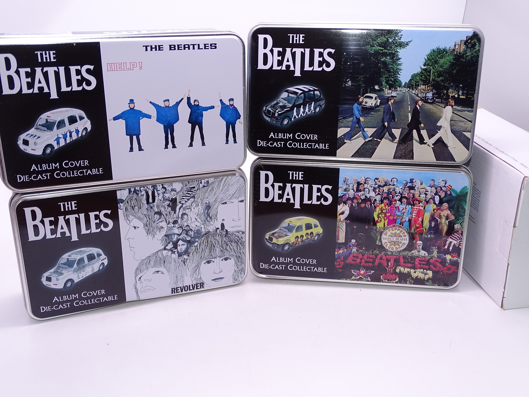 "Lot 2 - A group of Corgi ""The Beatles"" diecast London Taxis with Beatles album cover artwork, in collectable"