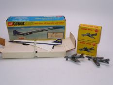 A Corgi Toys 650 diecast Concorde in BOAC blue/gold livery, together with a pair of Dinky fighter