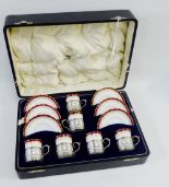 Lot 86 - Aynsley porcelain set of six demi tasse cups and saucers, the cups with silver mounts, in a fitted