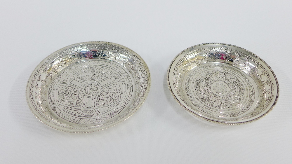 Lot 12 - Eastern silver circular trinket dish and a smaller white metal dish, largest 9.5cm diameter (2)