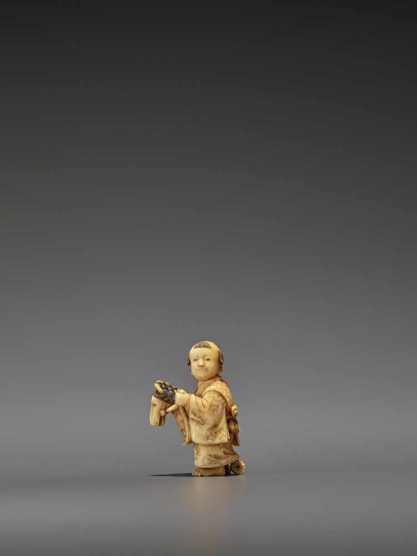 RYOMIN: A VERY FINE IVORY NETSUKE OF A BOY WITH HOBBY HORSE By Ono Ryomin, signed Ryomin with