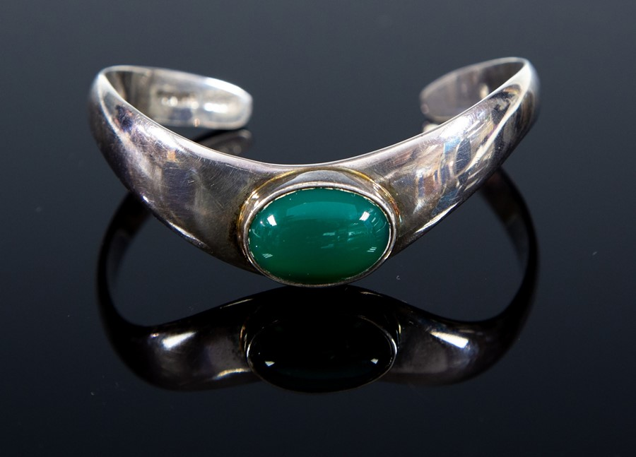 Lot 37 - A sterling silver bangle, set with an oval green cabochon stone, London import marks 1991, total